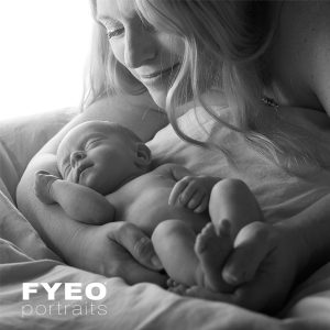 Mother and baby boudoir photoshoot. Picture showing a mother looking at her newborn baby, 10 days old.